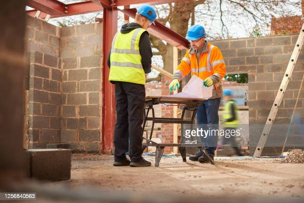 builder with apprentice - building exterior stock pictures, royalty-free photos & images