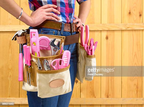 Builder with pink tools in belt