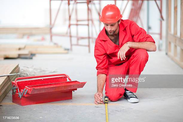 Builder with tool box and pencil measuring floor on construction site