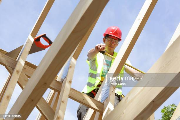 builder working on roof of house - roof stock pictures, royalty-free photos & images