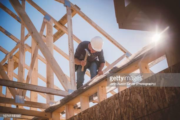 builder working on rooftop frame of building - bauen stock-fotos und bilder