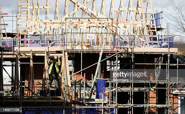 A builder works on the roof of a new house at a Barratt Homes development in Tyldesley UK on Thursday Feb 23 2012 UK house prices held their value...
