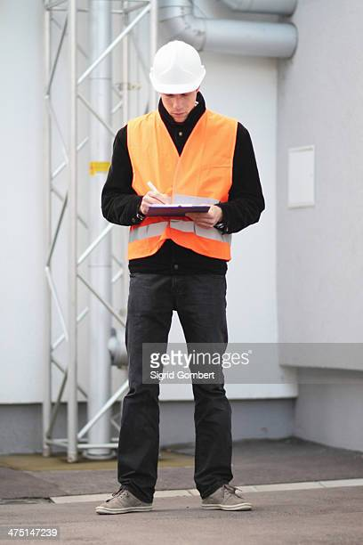 builder writing paperwork using clipboard - sigrid gombert stock pictures, royalty-free photos & images