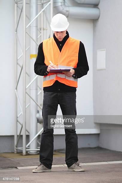 builder writing paperwork using clipboard - sigrid gombert - fotografias e filmes do acervo