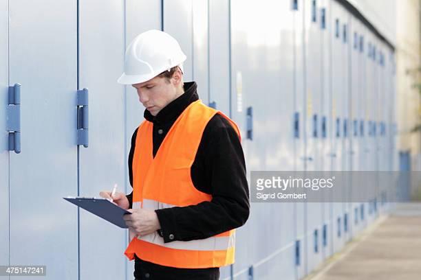 builder writing paperwork using clipboard - sigrid gombert imagens e fotografias de stock