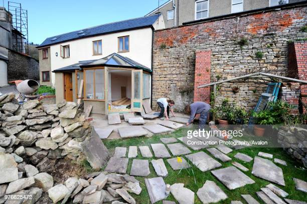 Builders lay out natural stone slabs in planning a patio, Gloucestershire UK.
