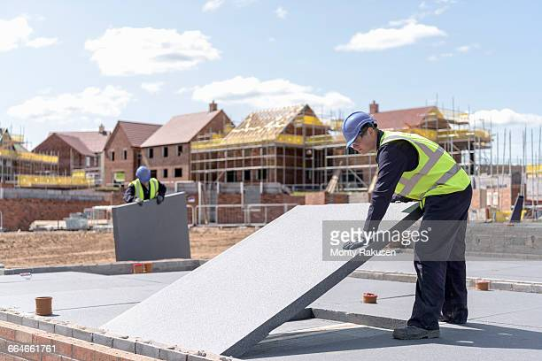 Builders laying insulation on housing building site