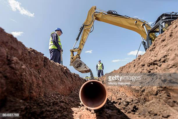 builders laying pipework on housing building site - gräva bildbanksfoton och bilder