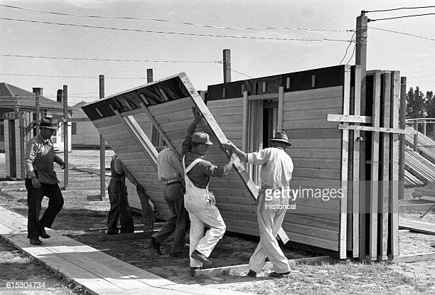 Builders making prefabricated houses for the Farm Security Administration Southeastern Missouri project for the rehabilitation of farm labor raise a...