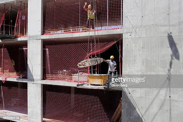 Builders move building material into a skip while working on a social housing site under development by Spanish construction company Sacyr SA in...