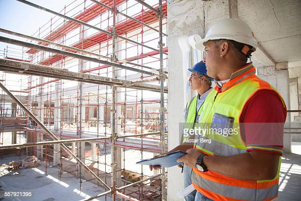 builders on construction site - construction stock pictures, royalty-free photos & images