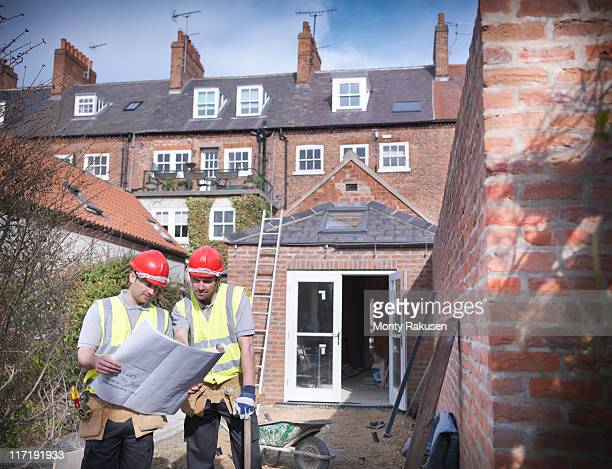 Builders outside house with plans
