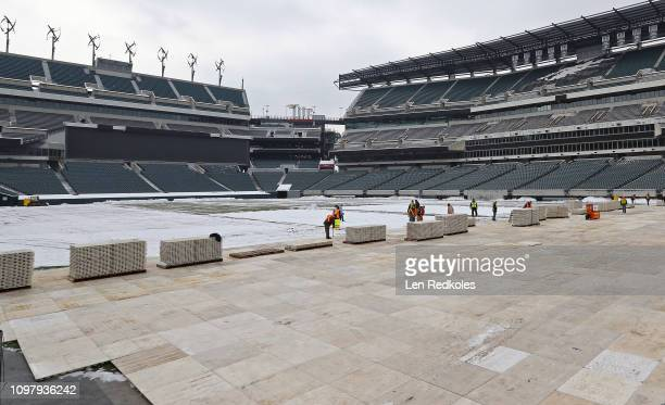 Builders start the process in covering the field with decking in preparation for the 2019 Coors Light NHL Stadium Series between the Philadelphia...