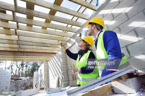 Builders taking measurement in unfinished building