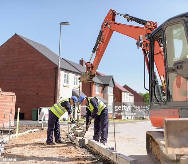 Builders using digger to lift kerb stones on housing building site