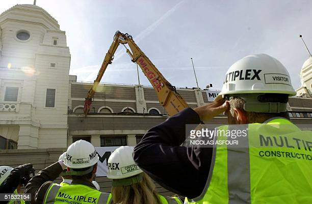 Builders visitors and the press look at a mechanical shear demolish 30 September 2002 the old Wembley stadium in London which will be rebuilt and...