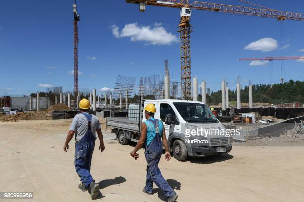 Builders wearing safety helmets going in front of Fiat Ducato pickup car standing under the Baukrane crane on the new building construction site are...