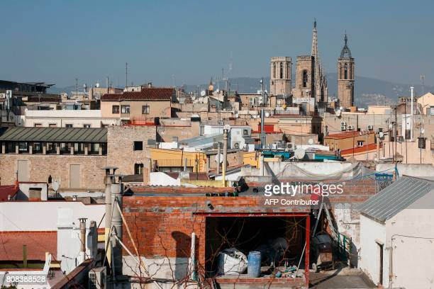Builders work on a waterproof roof of a building of El Gotic neighborhood with the Cathedral in background, in Barcelona on February 17, 2017. Hordes...