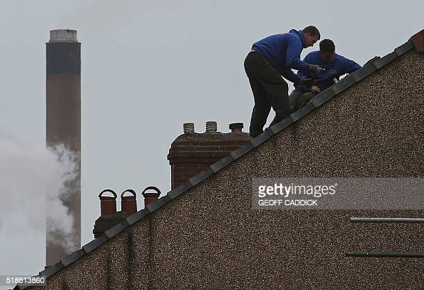 Builders work on the roof of a residential property near the Tata Steel steel plant at Port Talbot south Wales on April 1 2016 Shockwaves rippled...