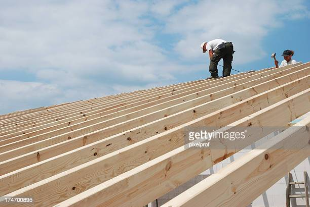 Builders working on constructing a roof