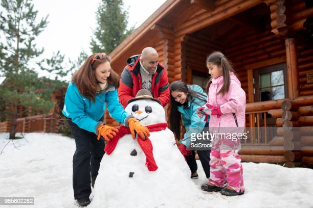 building a snowman - snowman stock pictures, royalty-free photos & images