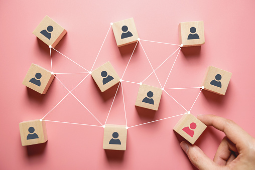 Building a strong team, Wooden blocks with people icon on pink background, Human resources and management concept. 1163789606