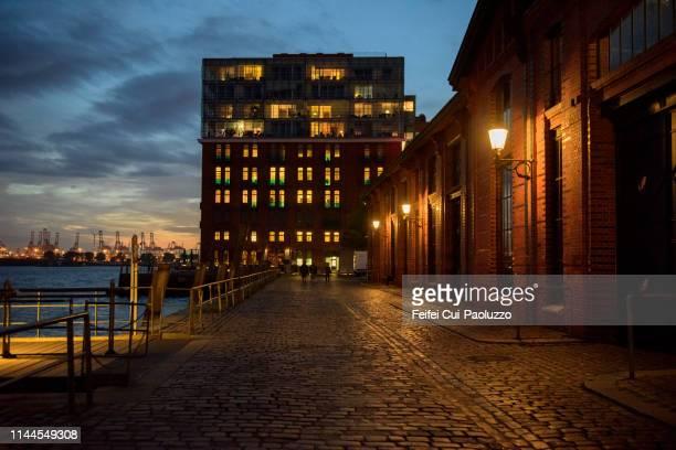 building and quayside of port of hamburg, germany - abenddämmerung stock-fotos und bilder