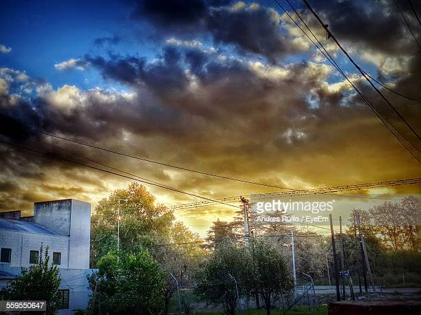 building and trees against cloudy sky at sunset - andres ruffo stock pictures, royalty-free photos & images