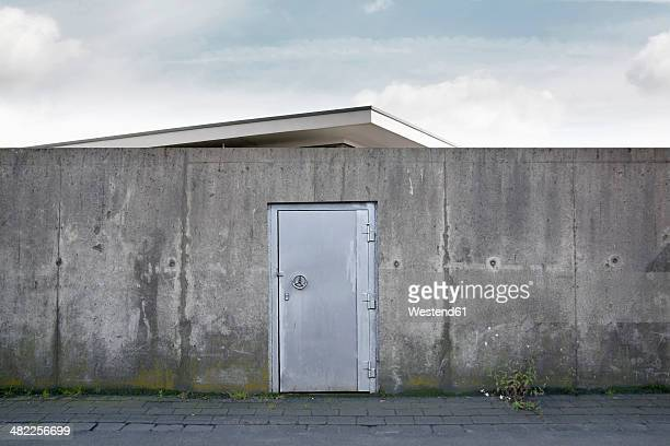 Building behind a wall with a safety door, composing