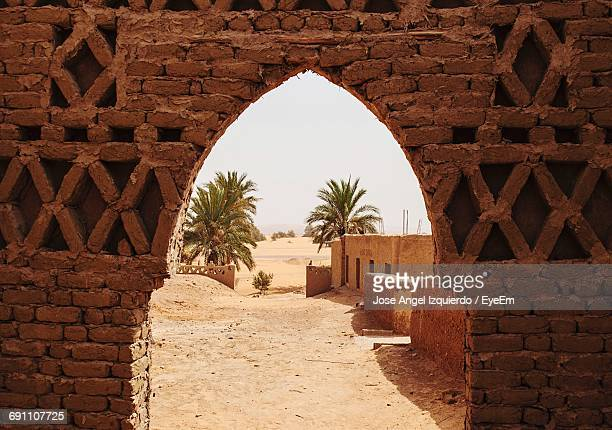 building by palm trees seen from archway in brick wall - merzouga stock pictures, royalty-free photos & images