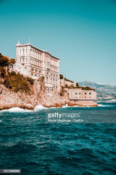 building by sea against clear blue sky - monaco stock pictures, royalty-free photos & images