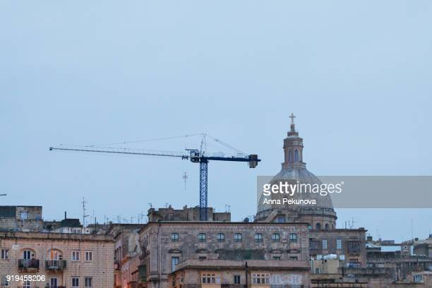 Building crane against blue sky, Valletta, Malta