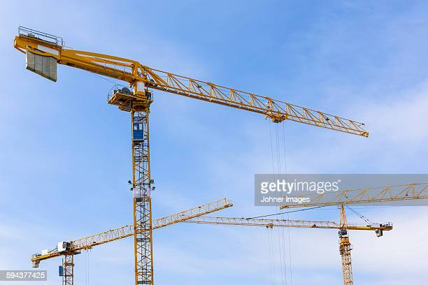 Building cranes against sky