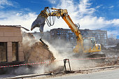 Building demolition machine pulls down a wall on a sunny day
