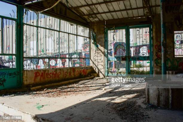 A building destroyed by Israeli raids and bombs seen next to the Separation Wall The Israeli Separation Wall is a dividing barrier that separates the...