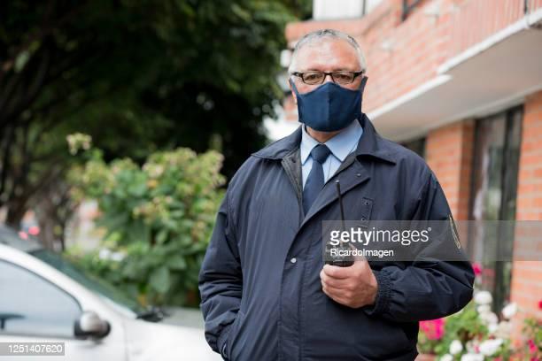 建物のドアマンは、covid 19を避けるためにマスクを着用しながら、肖像画でカメラを見ます - 警護する ストックフォトと画像
