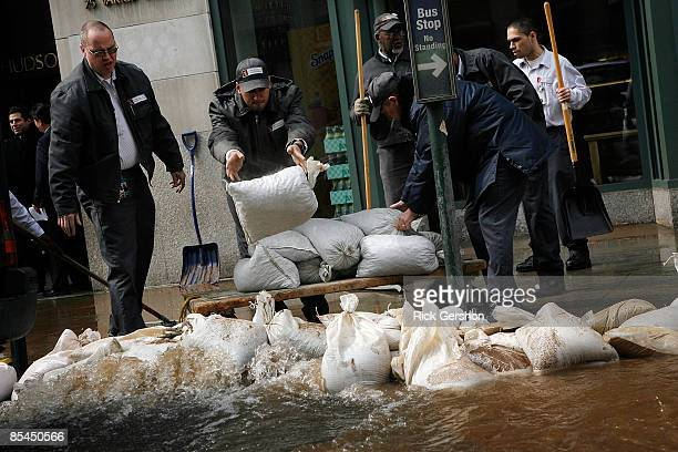 Building employees work to clean up flooding from a water main break that flooded portions of Varick Street just outside of the One Hudson Square...