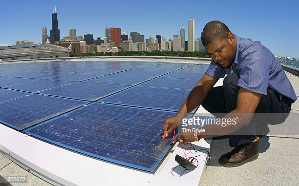 Building engineer Ernst Loubeau performs a diagnostic maintenance procedure July 5 2001 on the solar electric system located on the roof of the Field...