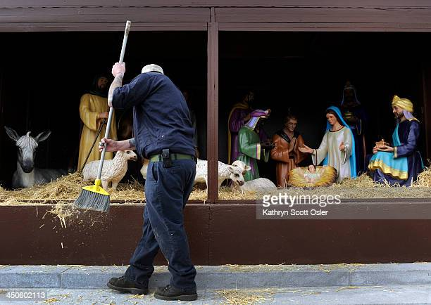 Building engineer Michael Spratt brushes off some of the extra hay as he and fellow crew members from the City and County of Denver place the figures...