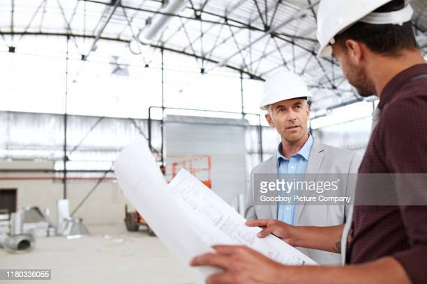 building engineers talking together over blueprints during a worksite inspection - real estate developer stock pictures, royalty-free photos & images