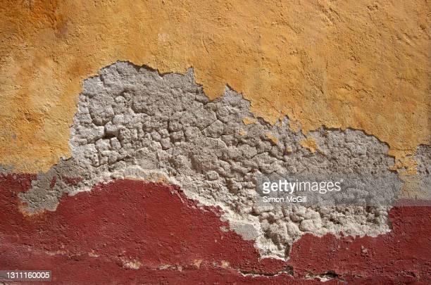 building exterior concrete stucco wall with peeling yellow dark red paint - geruïneerd stockfoto's en -beelden