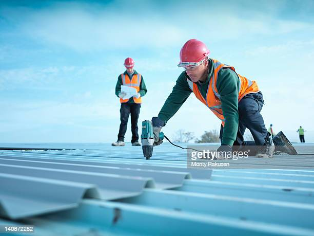 building foreman reading plans as workman insulates factory roof - kingston upon hull stock pictures, royalty-free photos & images