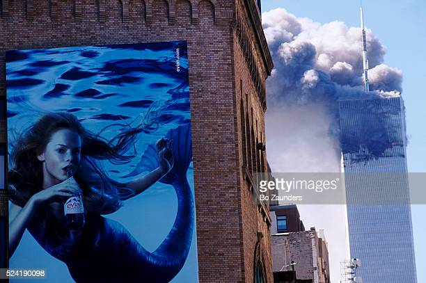 A building in Lower Manhattan advertises Evian bottled water as in the distance smoke billows from one of the Twin Towers during the 2001 terrorist...