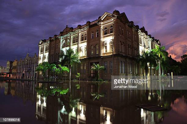 A building in the city centre is reflected in flood water at dusk on January 6 2011 in Rockhampton Australia Floodwaters peaked at 92 metres...