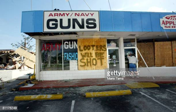 """Building inspector peeks into a store next to a gun shop with a makeshift sign reading """"Looters Will Be Shot"""" August 15, 2004 in Port Charlotte,..."""