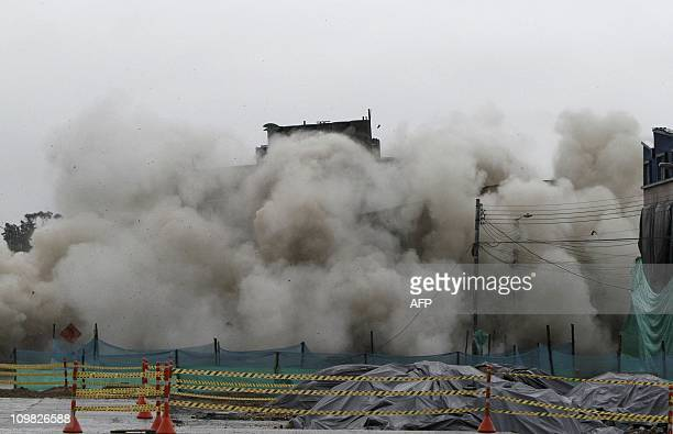 A building is being demolished by controlled explosions on March 6 2011 in Bogota 25 kilos of explosives were employed in the demolition carried out...