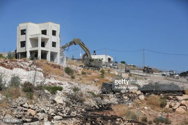 A building is being demolished with bulldozers under Israeli soldiers supervision as they have started to demolish buildings belonging to...