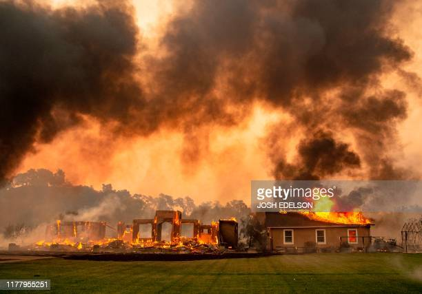 TOPSHOT A building is engulfed in flames at a vineyard during the Kincade fire near Geyserville California on October 24 2019 fastmoving wildfire...