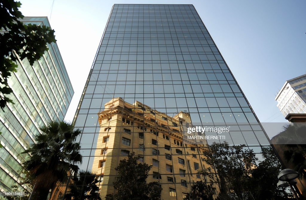 A building is reflected on a more modern one in downtown Santiago, on April 24, 2009. AFP PHOTO/Martin Bernetti /