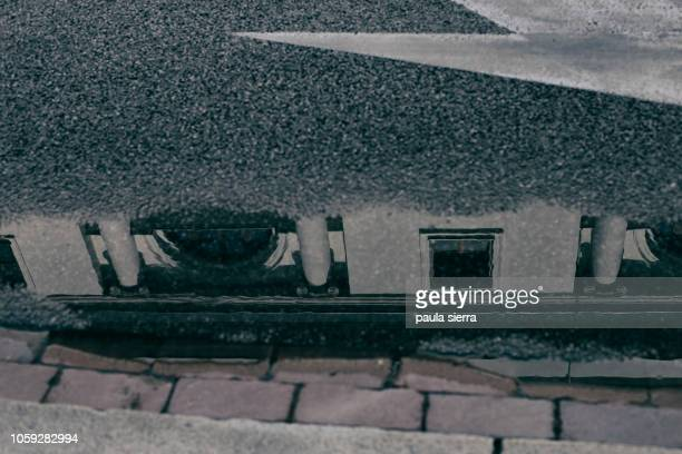 A building is reflected on a puddle
